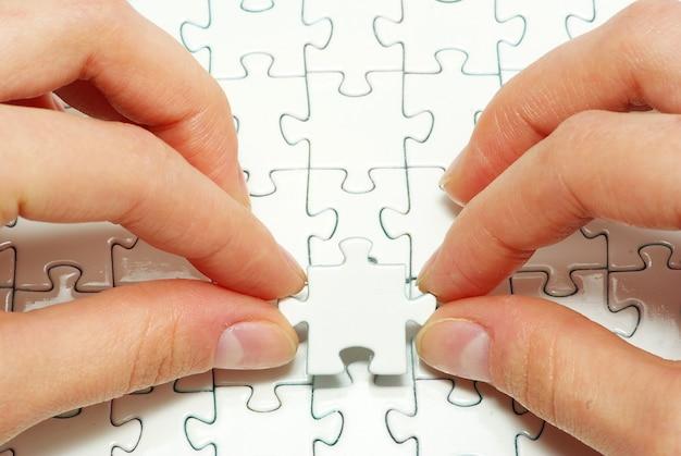 Mãos segurando uma peça do quebra-cabeça em branco