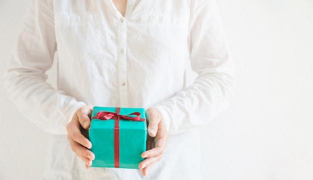 Mãos segurando uma pequena caixa de presente