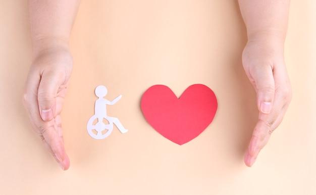 Mãos segurando uma pessoa recortada em papel sentada em uma cadeira de rodas