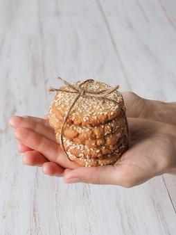 Mãos segurando uma pilha de biscoitos de gergelim frescos