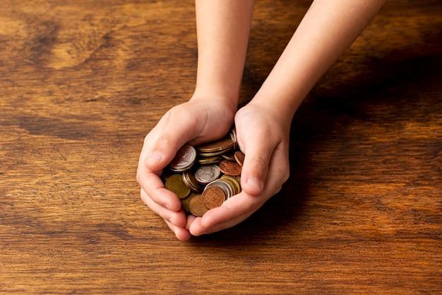 Mãos segurando uma pilha de moedas
