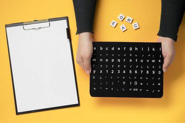 Mãos segurando uma placa do alfabeto braille