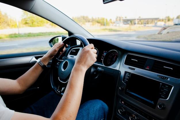 Mãos segurando uma roda de carro moderna