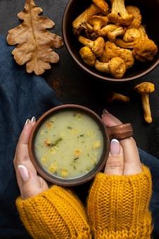 Mãos segurando uma sopa de cogumelos na xícara