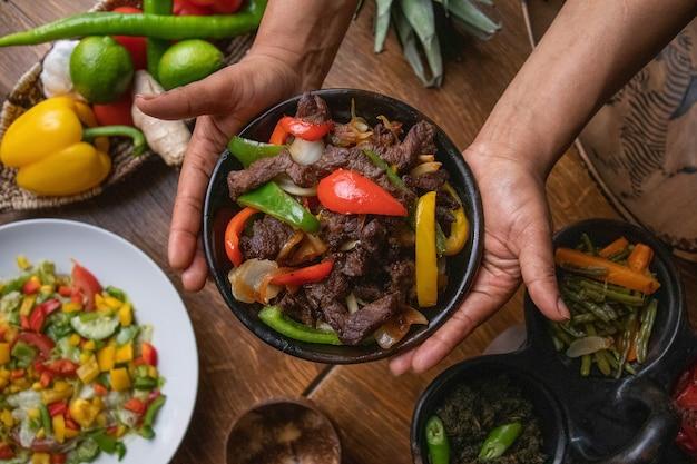 Mãos segurando uma tigela de fajita, comida mexicana