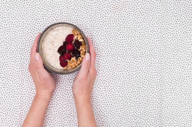 Mãos segurando uma tigela de granola