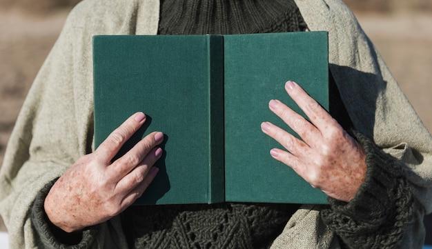 Mãos segurando uma vista frontal do livro aberto