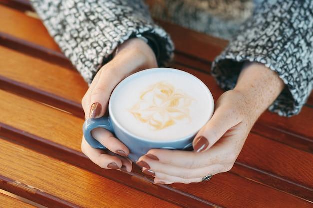 Mãos segurando uma xícara com café com leite branco quente