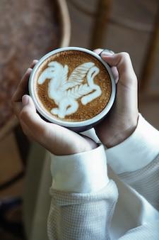 Mãos segurando uma xícara de café com leite com arte