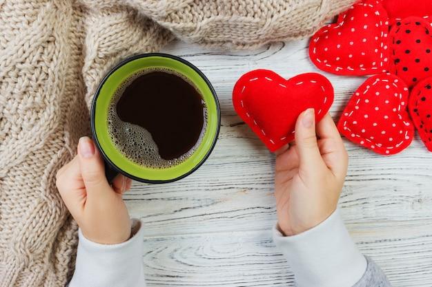 Mãos segurando uma xícara de café e coração de têxteis