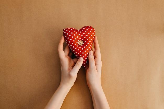 Mãos segurando vermelho com coração de bolinhas brancas.