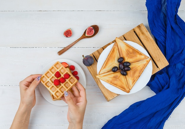 Mãos segurando waffle com bagas e frutas em um prato branco sobre uma superfície branca