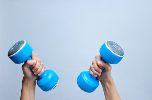 Mãos segurar halteres de plástico azuis na superfície cinza