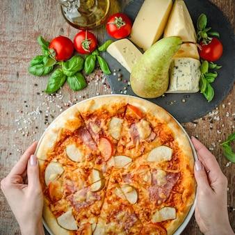 Mãos segurar pizza havaiana em uma mesa de madeira