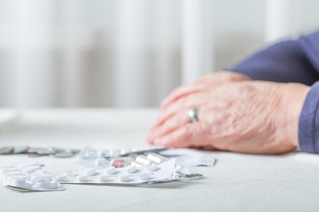 Mãos sênior da mulher do close up com comprimidos e moedas na tabela em casa. um idoso aposentado conta dinheiro.