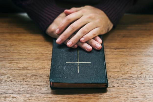 Mãos sobre a bíblia na mesa de madeira