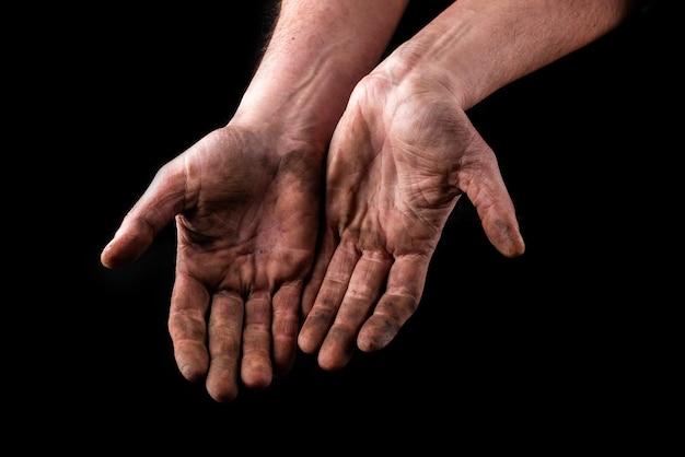Mãos sujas isoladas em preto. mãos implorando.