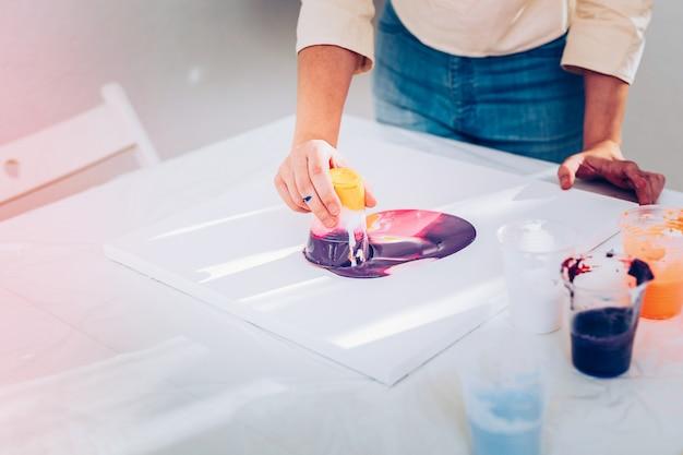 Mãos sujas. jovem artista criativa se sentindo inspirada por sujar as mãos enquanto pintava mármore