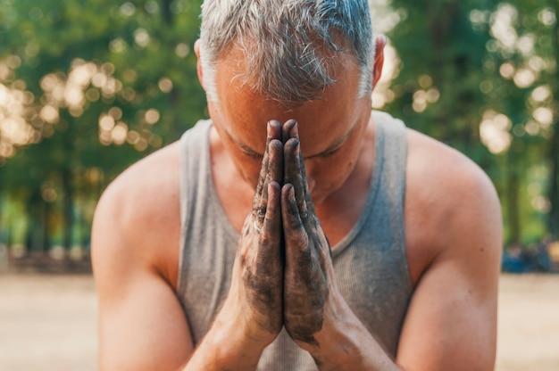 Mãos sujas juntas para uma oração. o homem reza com a cabeça baixa e as mãos togeth