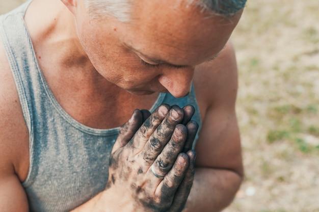 Mãos sujas juntas para uma oração