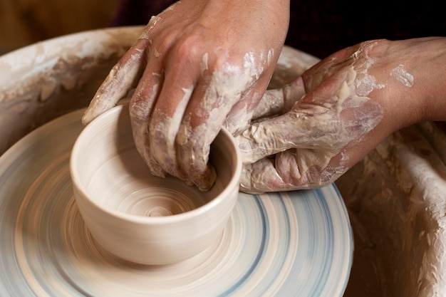 Mãos sujas modelando em argila em uma roda de oleiro