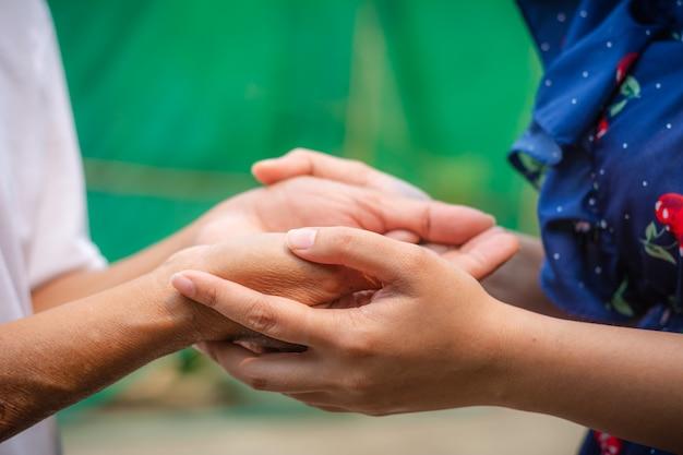 Mãos superiores e asiáticas novas asiáticas que guardam.