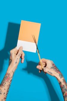 Mãos tatuadas cortando um papel amarelo com uma parede azul