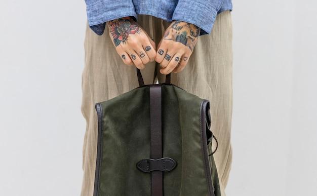 Mãos tatuadas segurando uma bolsa verde
