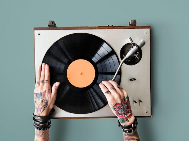 Mãos tatuadas tocando em um toca-discos de vinil