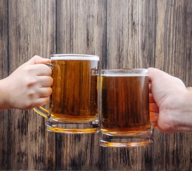 Mãos tinindo canecas de cerveja na vista lateral de madeira rústica
