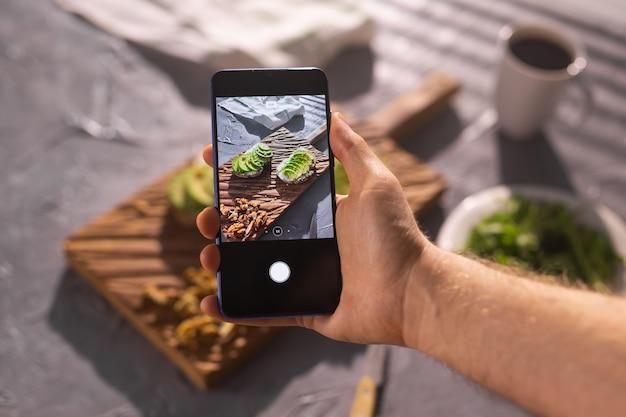 Mãos tiram fotos no smartphone de dois lindos sanduíches de creme azedo e abacate saudáveis mentindo