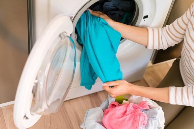 Mãos tirando a roupa na máquina de lavar roupa