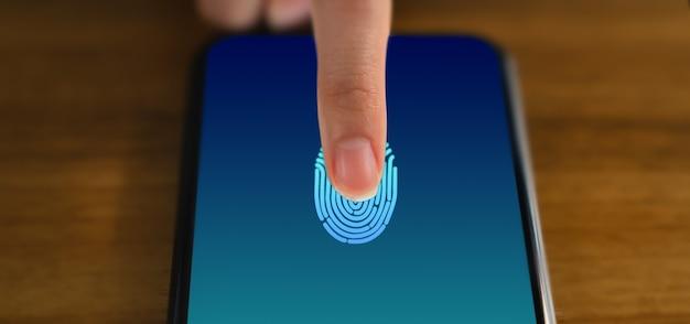 Mãos tocando smartphone e mostram a tela do scanner de impressão digital para acesso online.