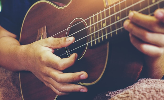 Mãos tocando violão ukulele acústico. show de habilidades musicais