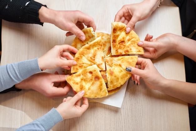 Mãos tomando fatias de tortilla com queijo cottage ou vertuta de uma placa de madeira, close-up