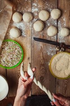 Mãos torcendo a massa para preparar a vista superior do bagel turco simit.