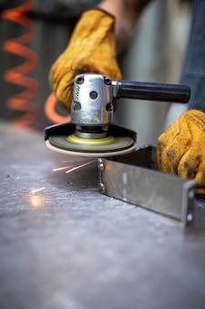 Mãos trabalham ferramenta de moedor em uma superfície de metal