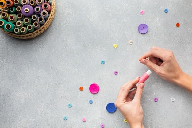 Mãos trabalhando com botões e linha de costura