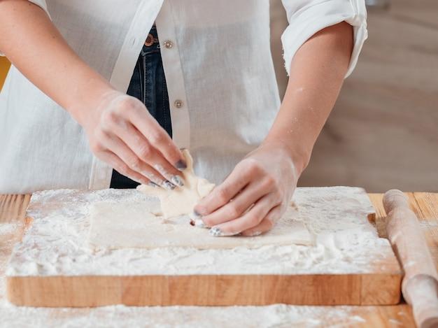 Mãos trabalhando com massa preparando biscoitos