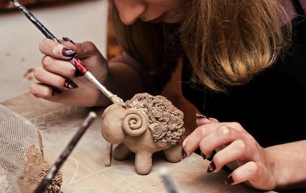 Mãos trabalhando e terminando a escultura com argila na mesa de madeira na oficina