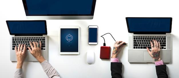 Mãos trabalhando em um laptop na mesa