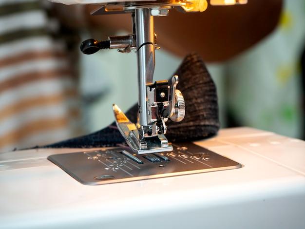 Mãos trabalhando na máquina de costura