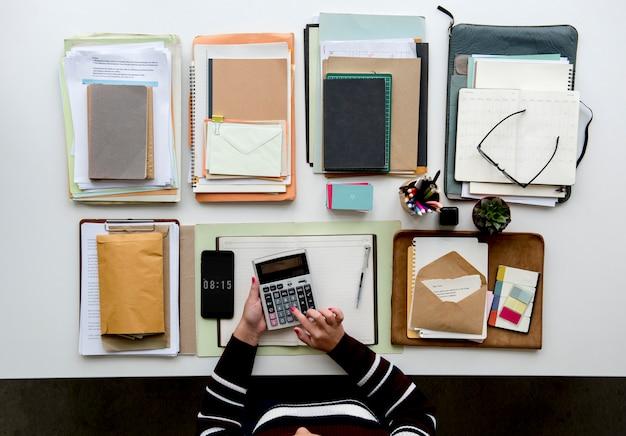 Mãos trabalhando na mesa de escritório com notebooks e artigos de papelaria na mesa branca