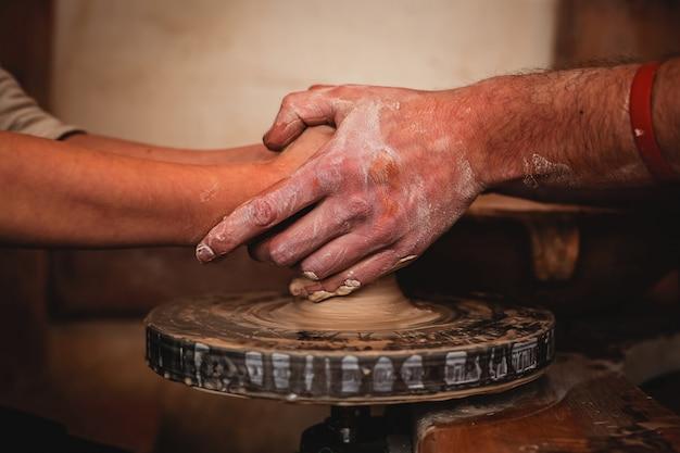 Mãos trabalhando na roda de oleiro