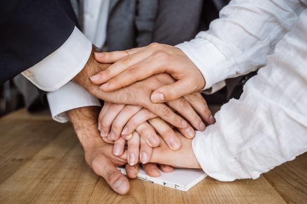 Mãos unidas da equipe de negócios sobre fundo de espaço de trabalho