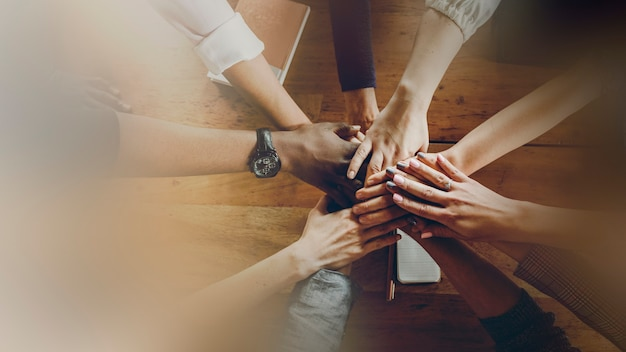 Mãos unidas sobre uma mesa de madeira