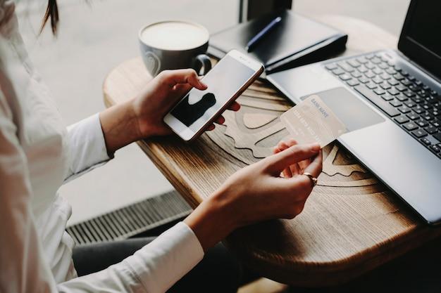Mãos usando cartão de crédito de plástico e smartphone para internet banking ou transação on-line, sentado à mesa de um café perto de uma janela.