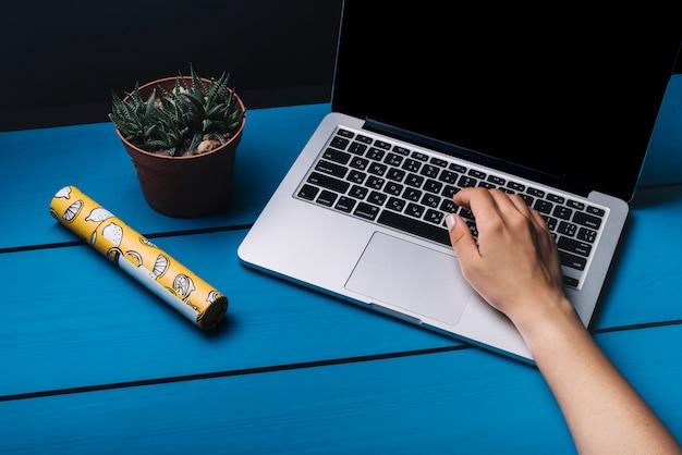 Mãos, usando, laptop, ligado, azul, escrivaninha
