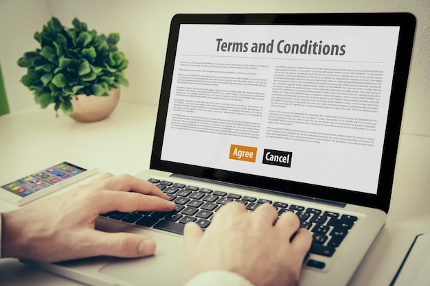 Mãos usando laptop no desktop com termos e condições