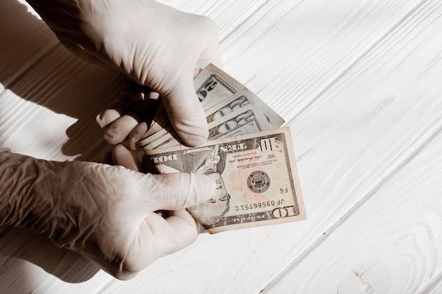 Mãos usando luvas de proteção e dólares